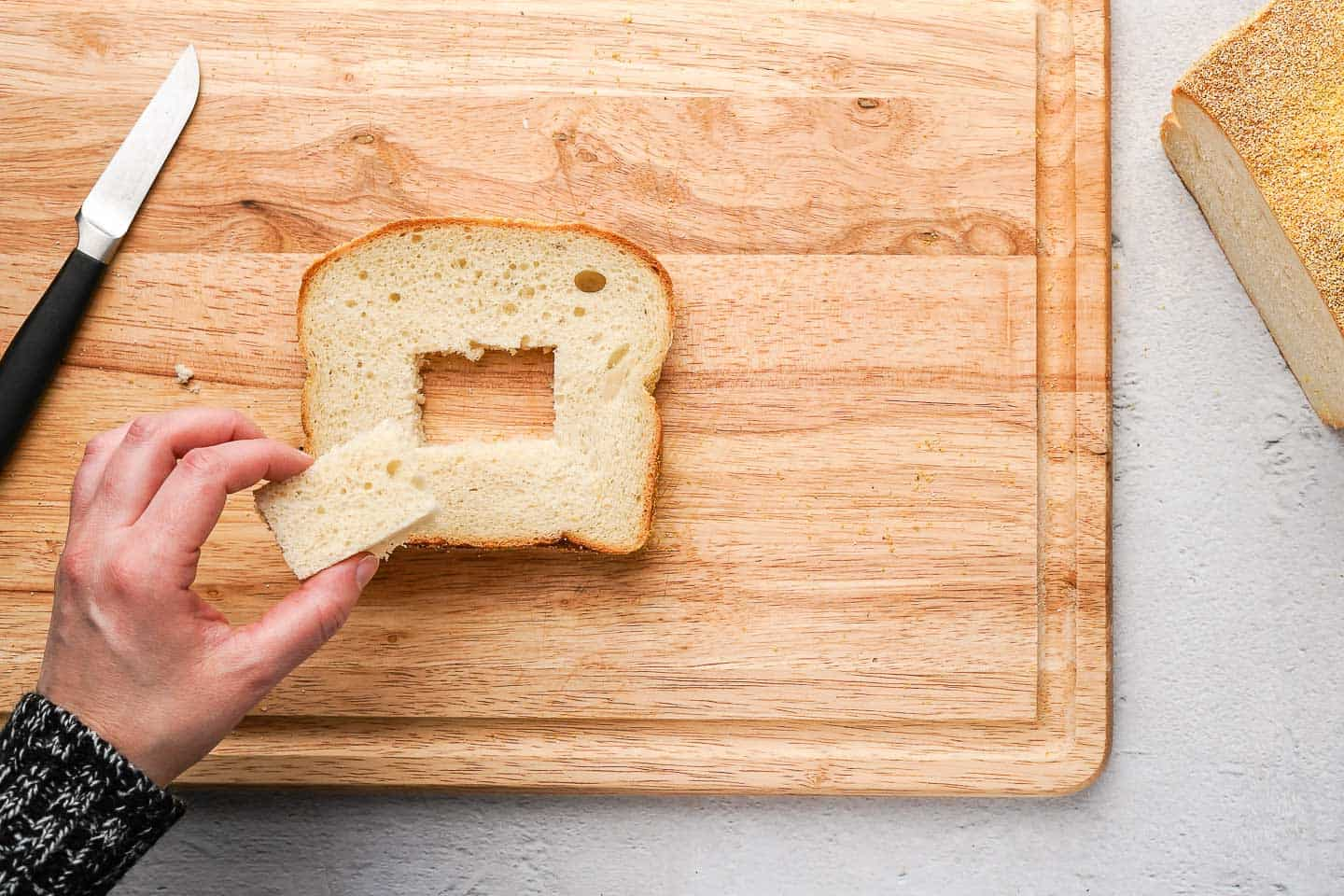 Hand holding a square of bread over top slice of bread