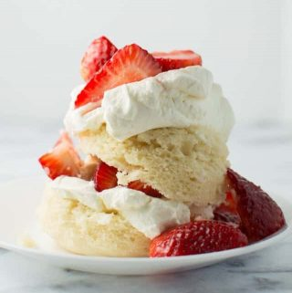 Side view of vanilla cake topped with strawberries and whipped cream