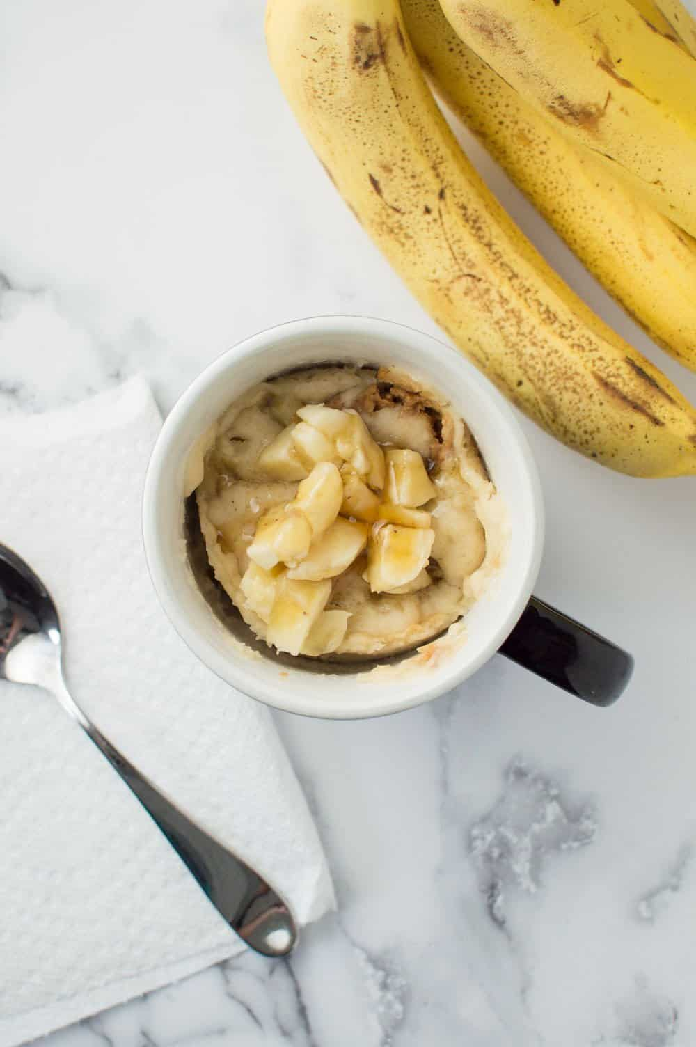 Top down view of mug cake with banana pieces on the top and a bunch of bananas on the side