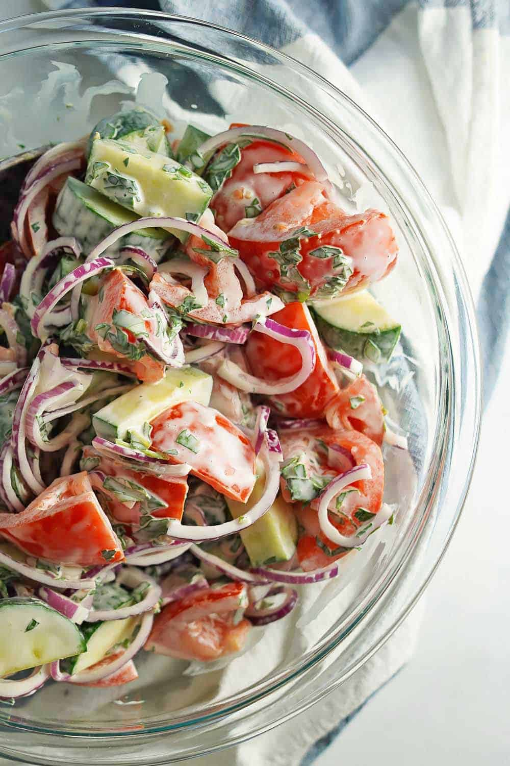 Creamy Tomato Cucumber Salad Close up view in glass bowl
