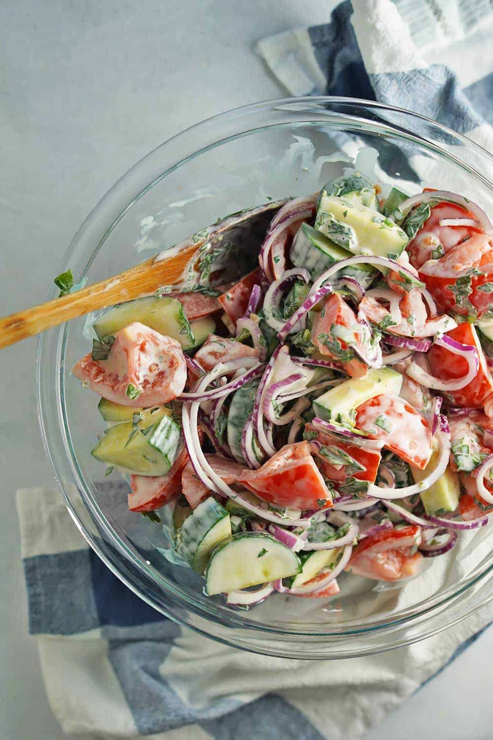 Creamy Tomato Cucumber Salad in glass bowl with wooden spoon