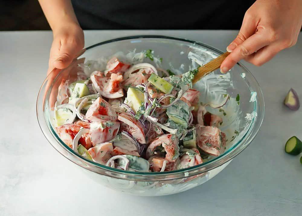 Mixing Creamy Tomato Cucumber Salad