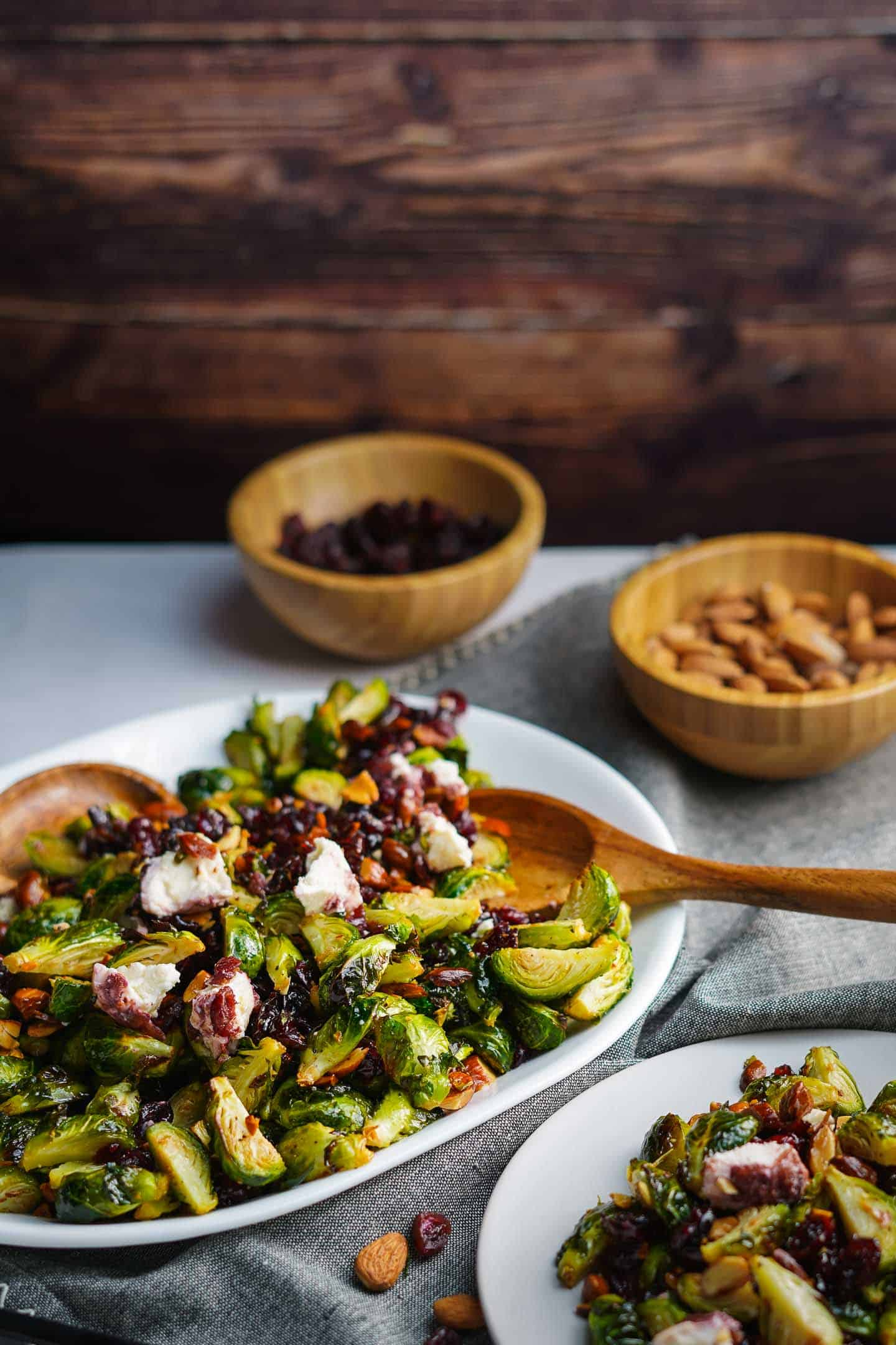 Brussels Sprout Salad with Cranberries on white platter with plate on the side