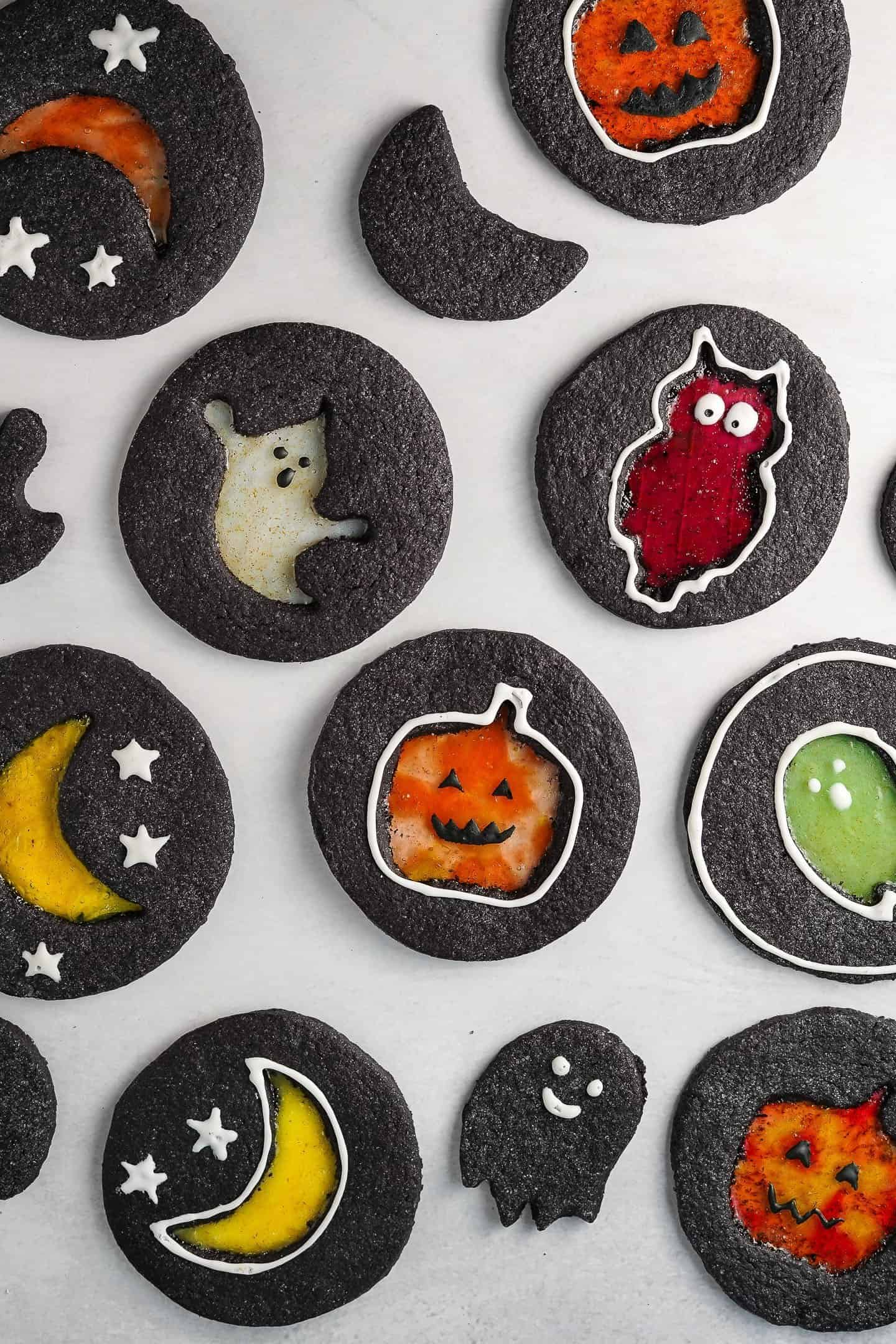 overhead view of black cookies with Halloween designs in the center laying on white surface