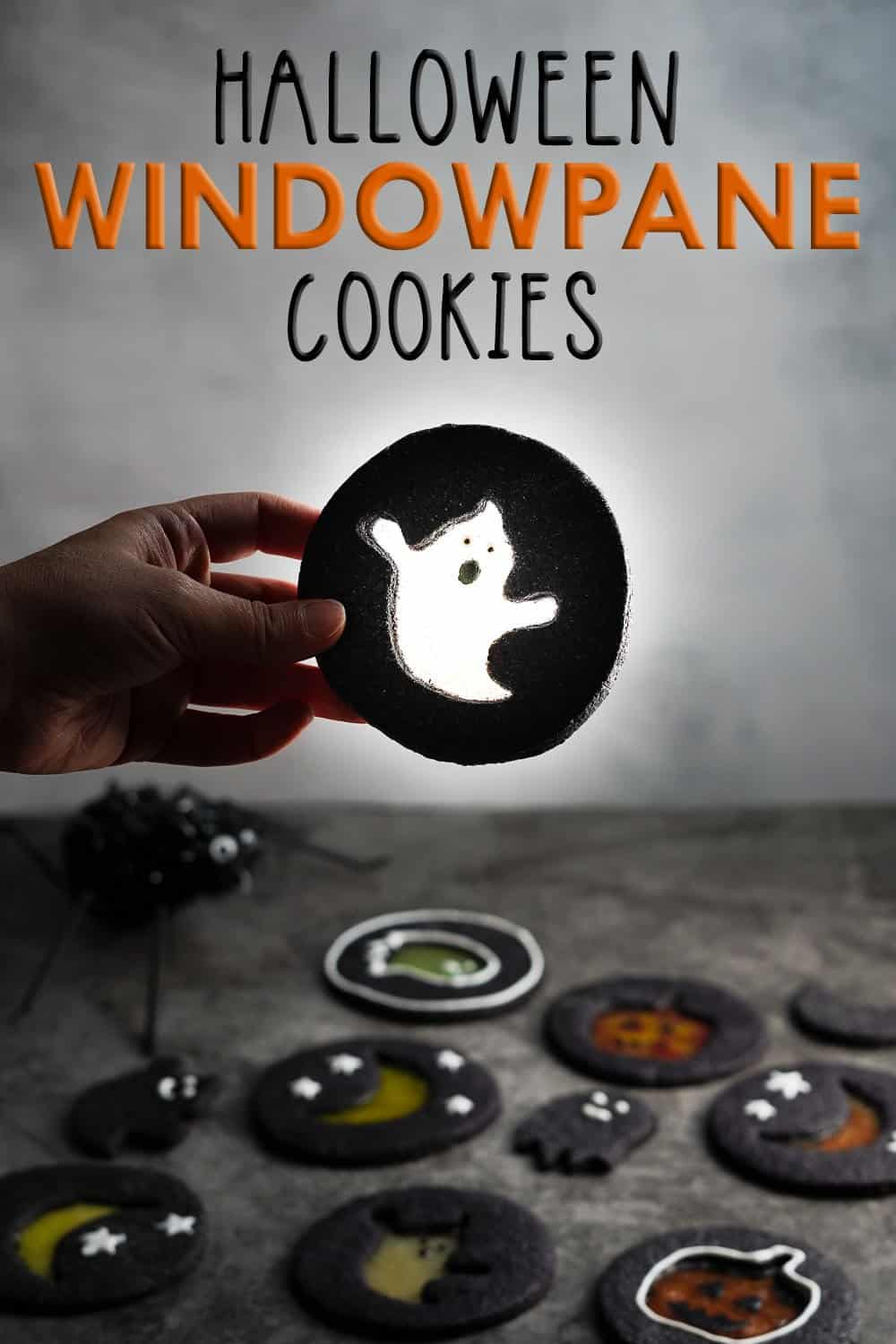 Hand holding black cookie with ghost design in the middle