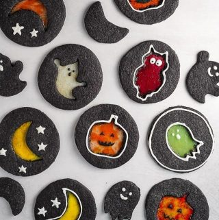 black cookies with multi colored Halloween designs in the center