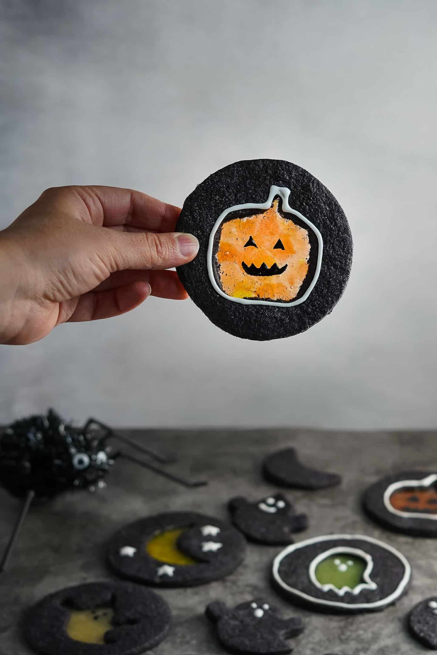 Hand holding black cookie with pumpkin design in the center