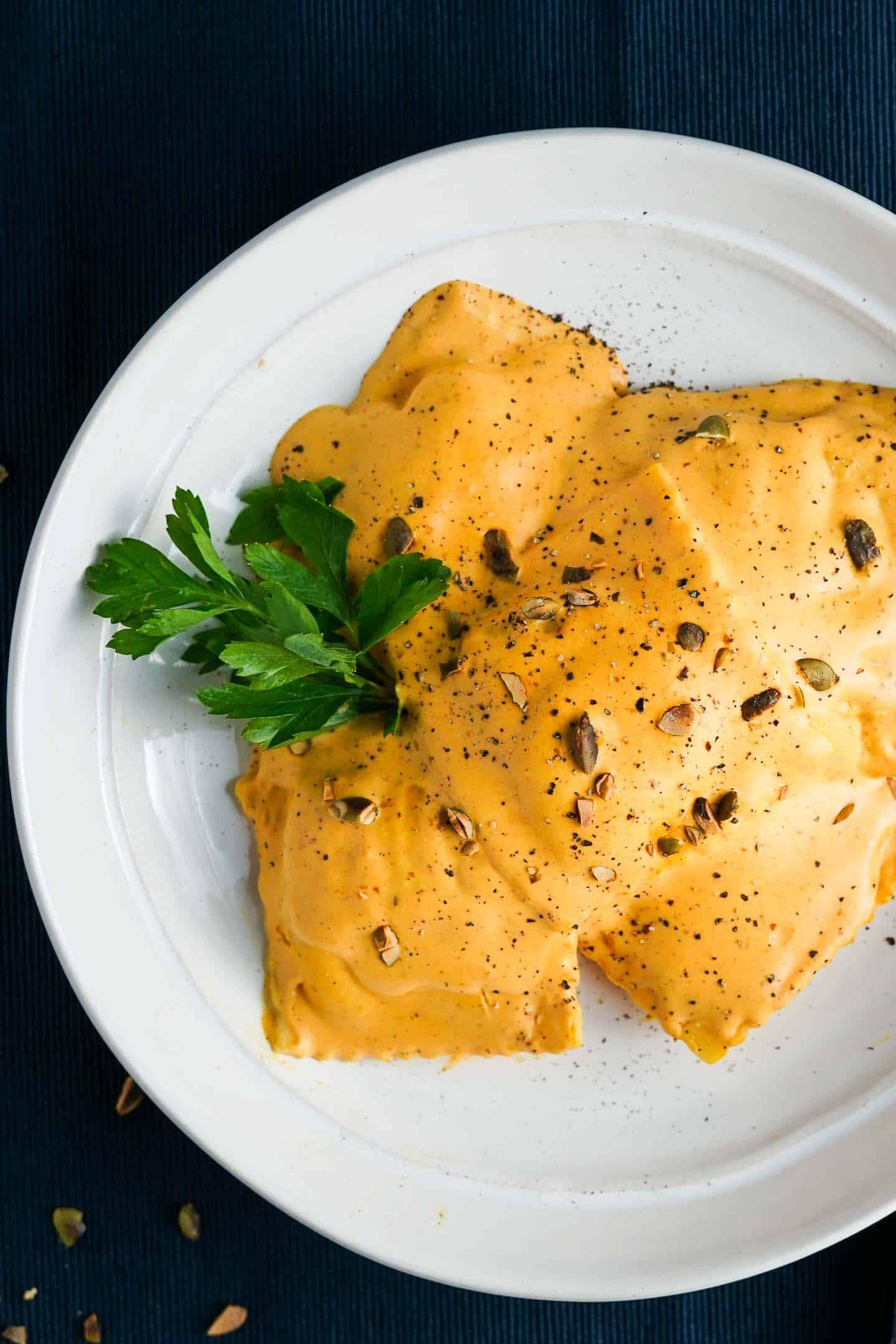 Ravioli with pumpkin cream sauce on white plate
