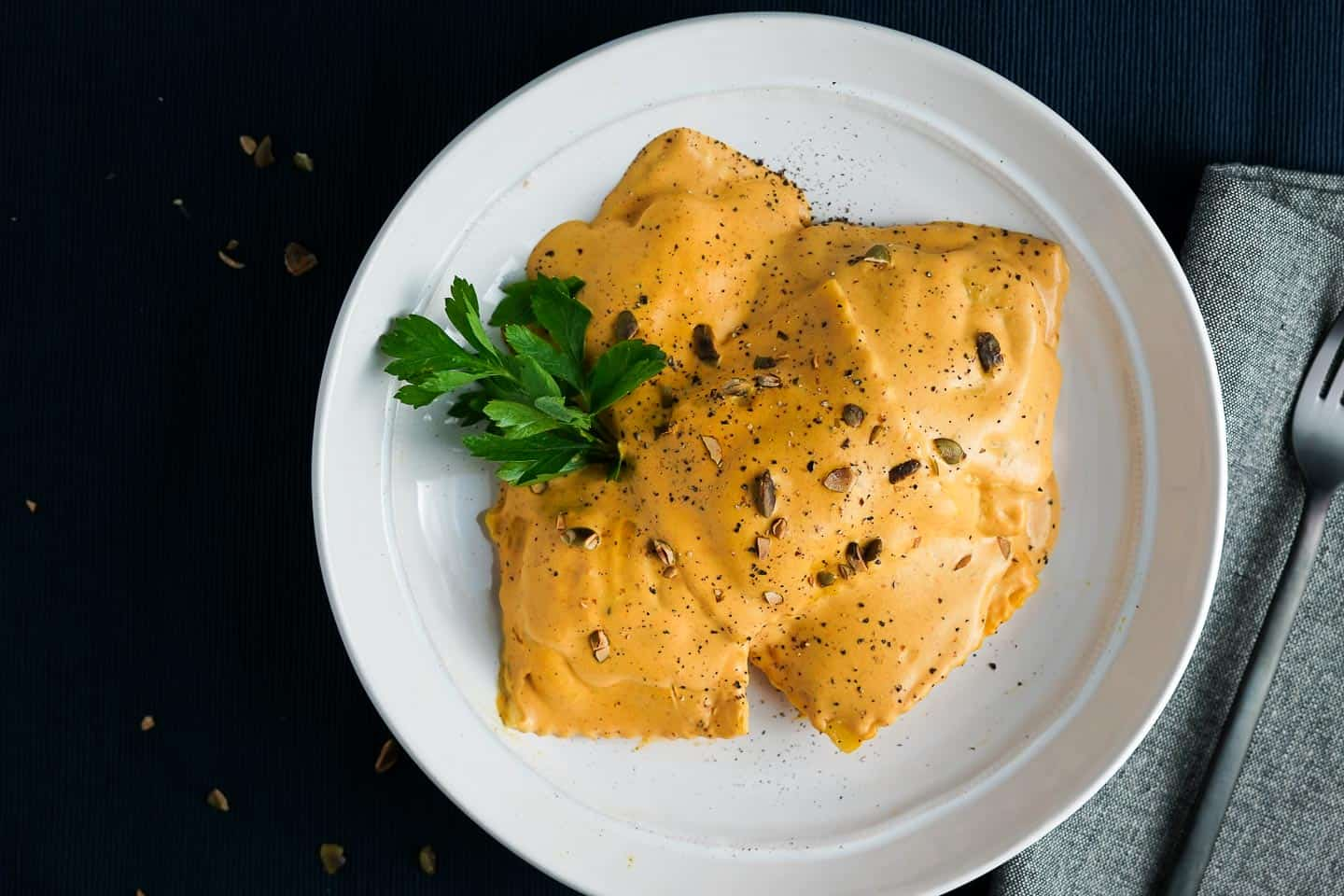 Ravioli with Pumpkin Cream Sauce on white plate with napkin and fork on the side