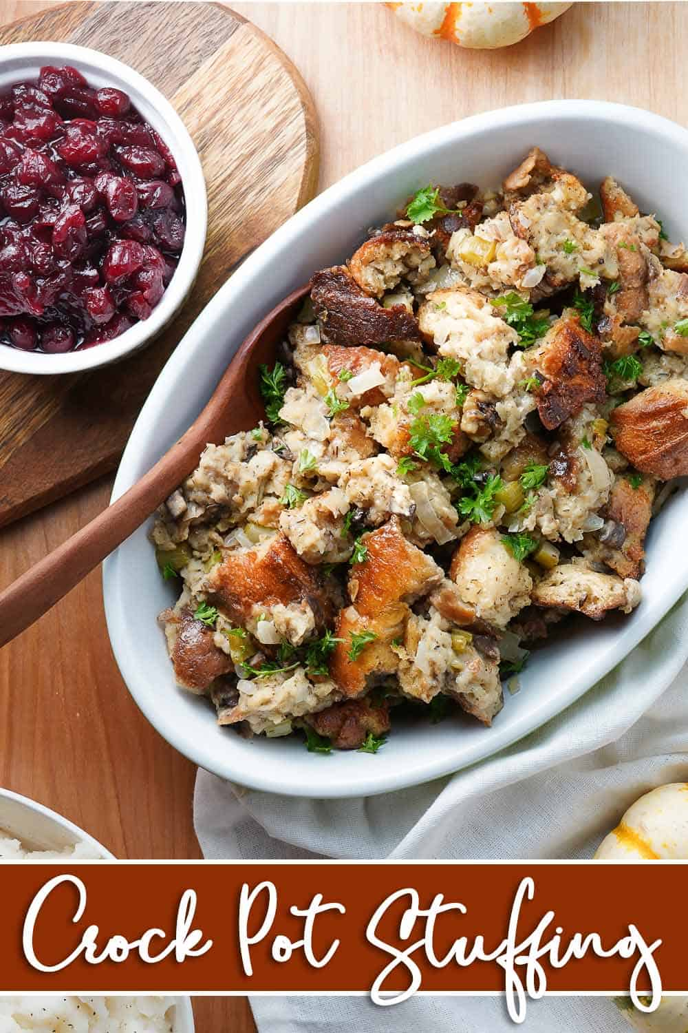 Crock Pot Stuffing in oval dish with cranberry sauce on the side
