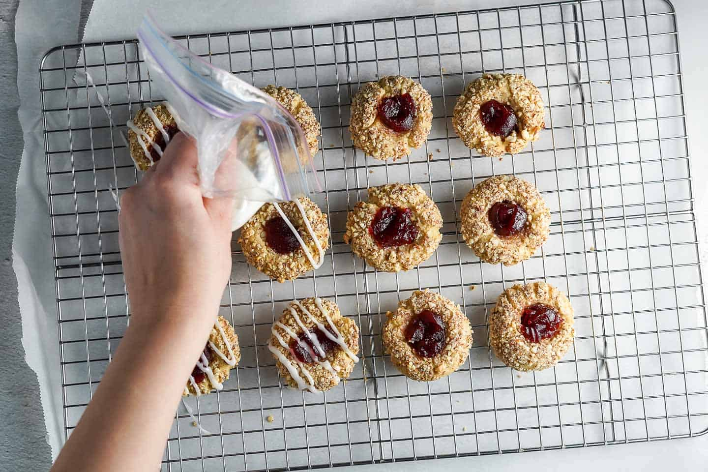 Squeezing Icing over Thumbprint Cookies