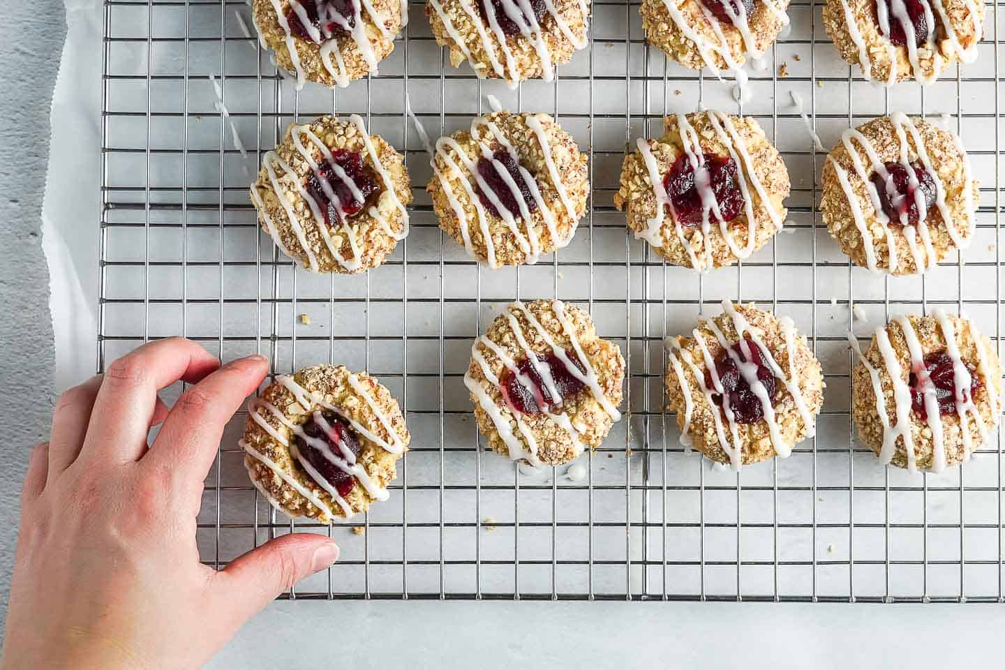 Thumbprint Cookies on Cooling Rack with hand taking cookie