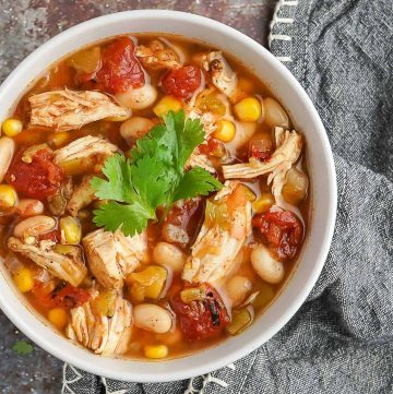 Easy Slow Cooker Chicken Chili in grey bowl with napkin on the side