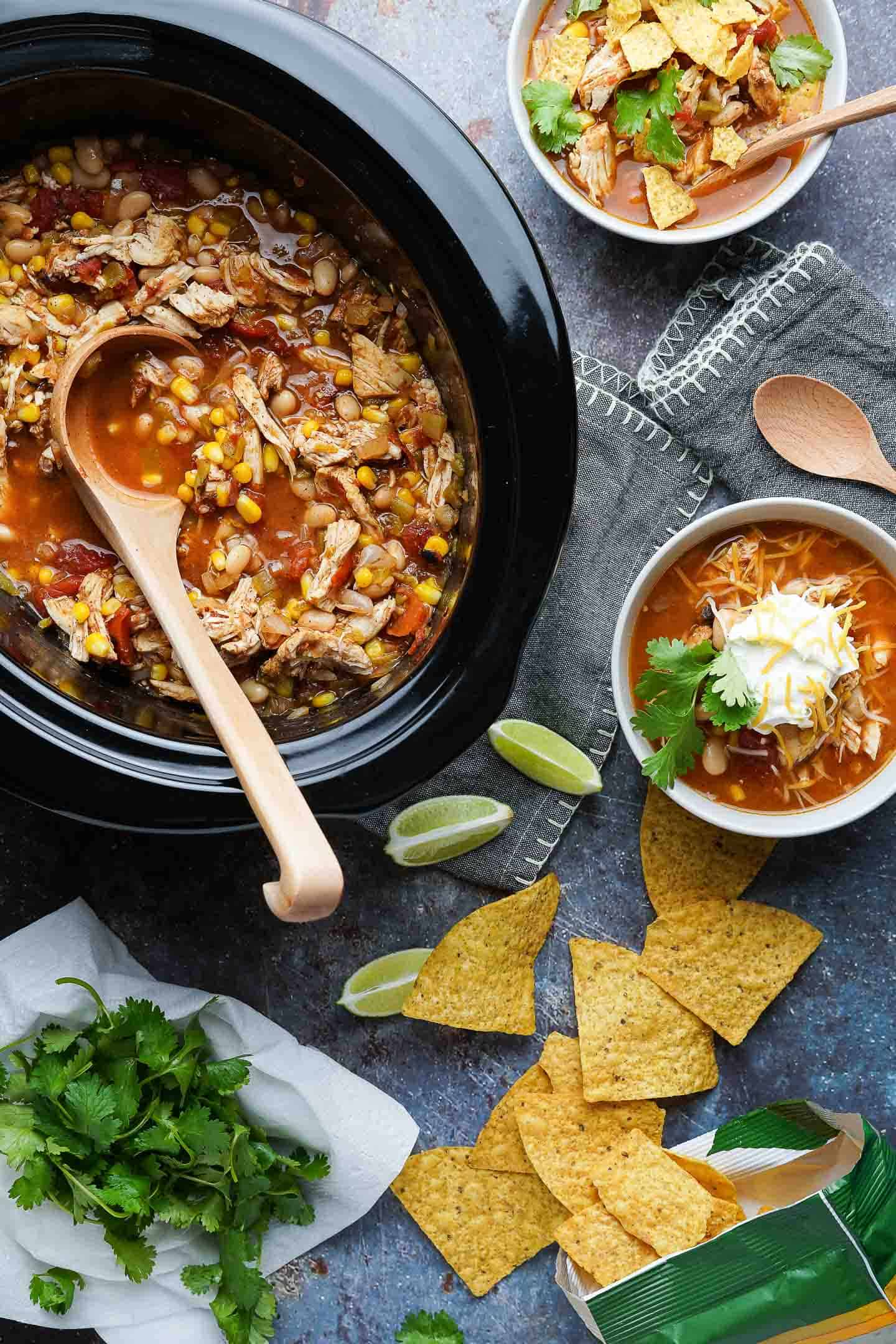 Easy Slow Cooker Chicken Chili in crockpot and two bowls with chips limes and cilantro on the side