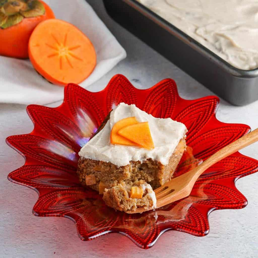 Persimmon Cake on orange plate with persimmon cake and persimmon in the background