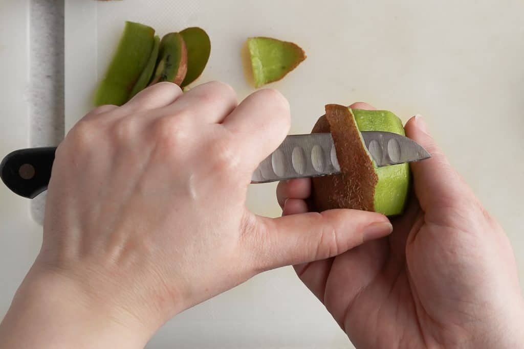 Holding Kiwi in Hand and Cutting Skin off with Paring Knife