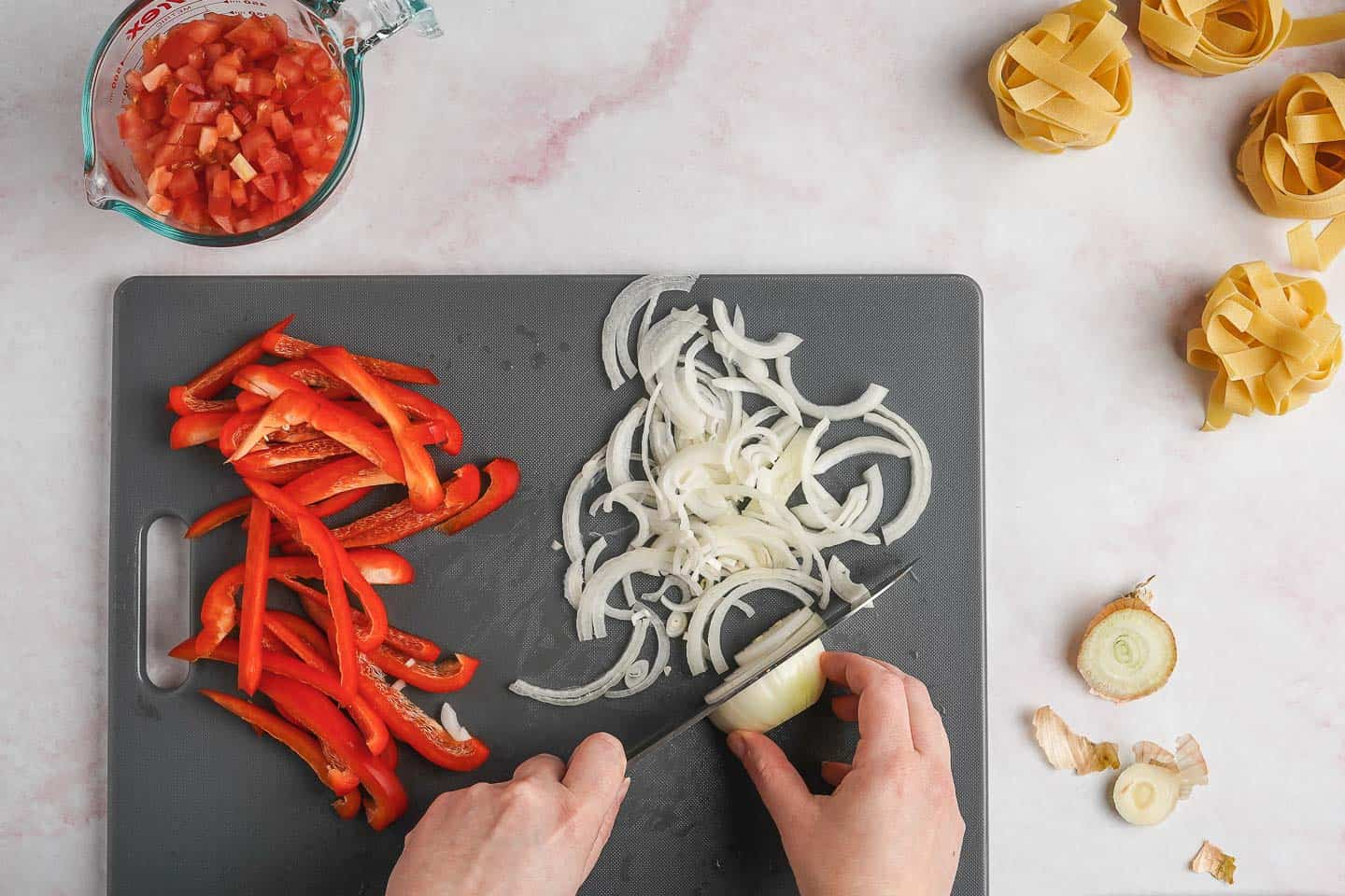 Cutting Onions and Bell Peppers on a Grey Cutting Board