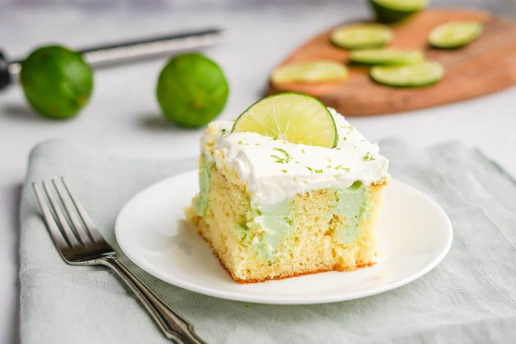 Key Lime Poke Cake on a Plate with Limes
