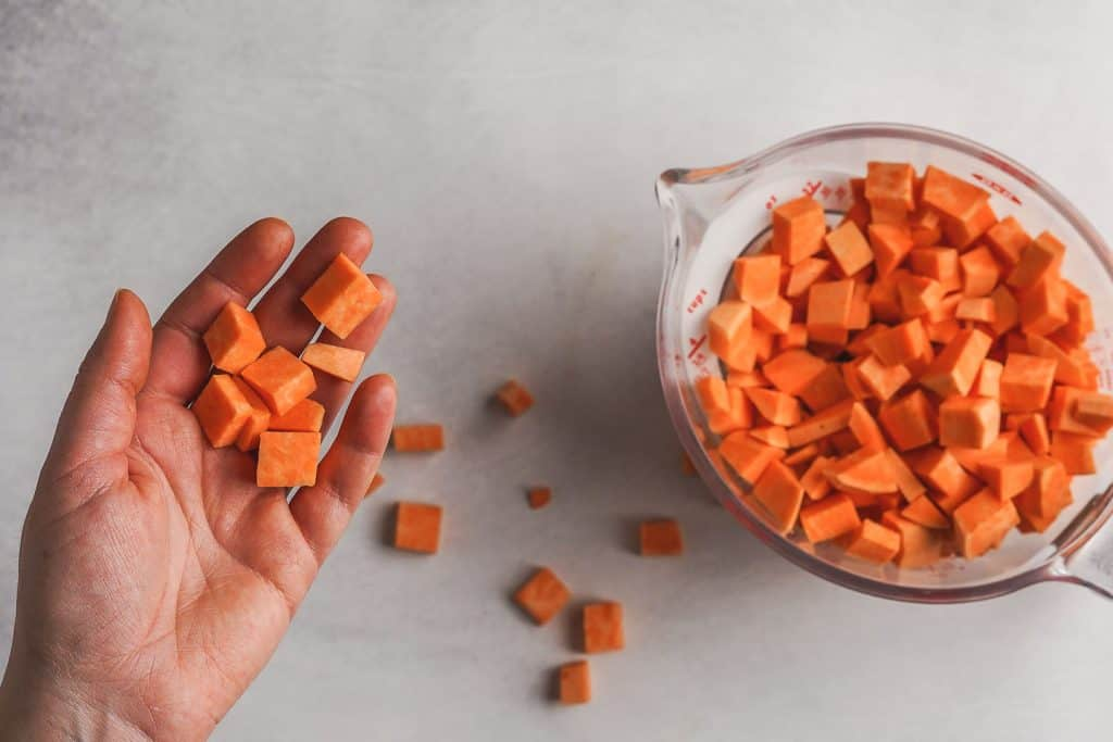 Sweet Potato Cubes in Hand and Measuring Cup