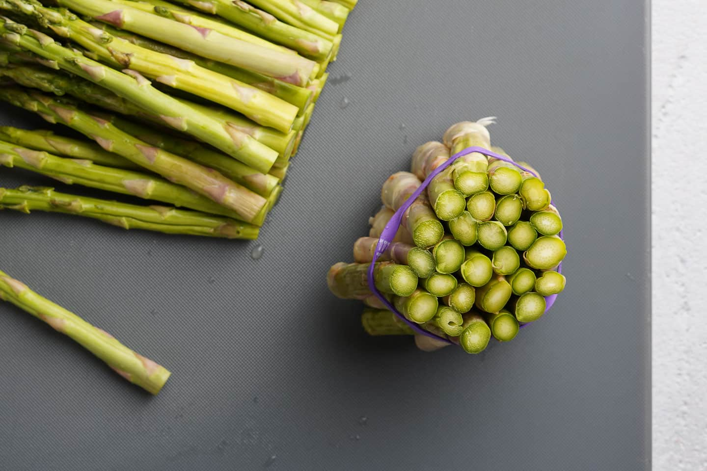 Bundled Ends of Cut off Asparagus on Cutting board