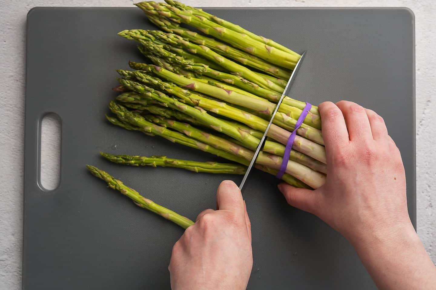 Knife cutting ends off a bunch of asparagus on a cutting board