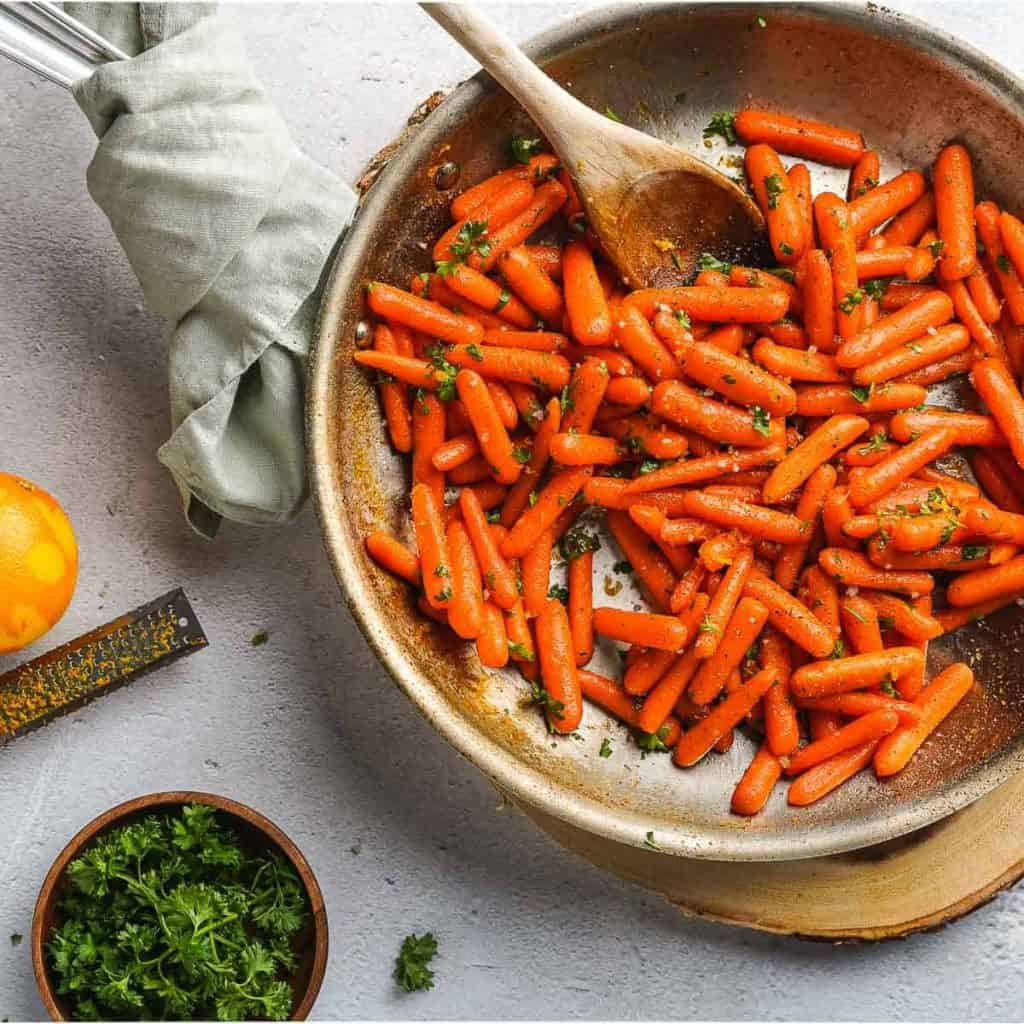Easy Honey Orange Glazed Carrots in pan with garnishes on the side