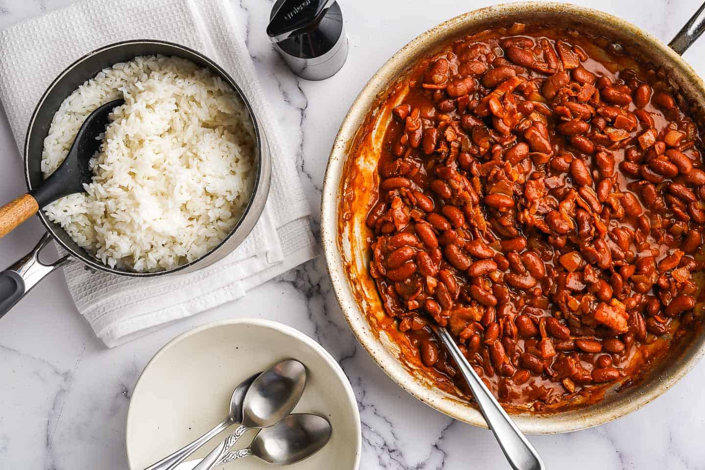 Red beans in skillet with rice and empty bowls on the side