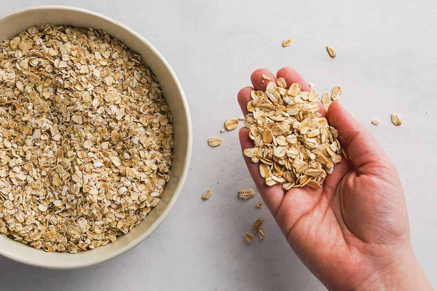 Bowl of quick oats next to hand holding old-fashioned rolled oats