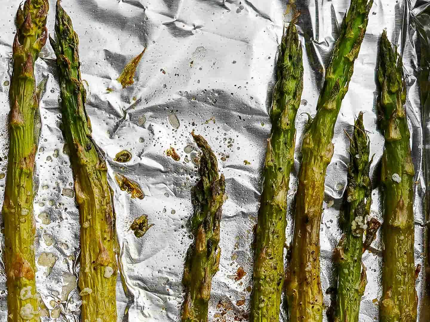 Close up view of roasted asparagus on aluminum foil