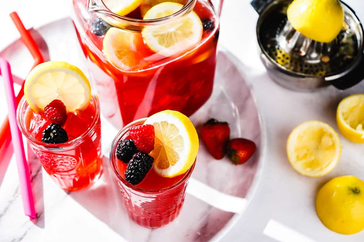 Berry Lemonade in pitcher and 2 glasses with lemon rinds on the side