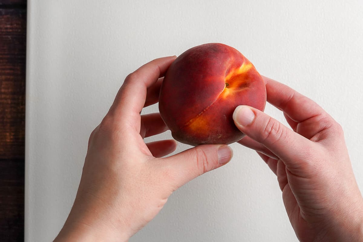 Two hands holding a ripe peach