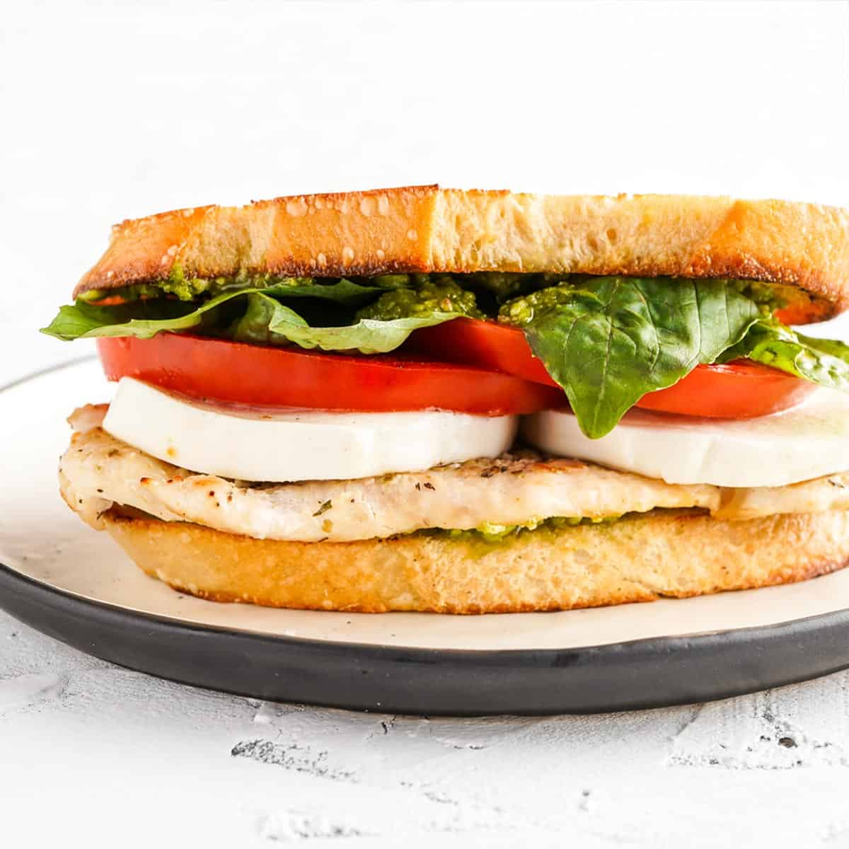 Close up side view of sandwich with basil mozzarella tomato and chicken