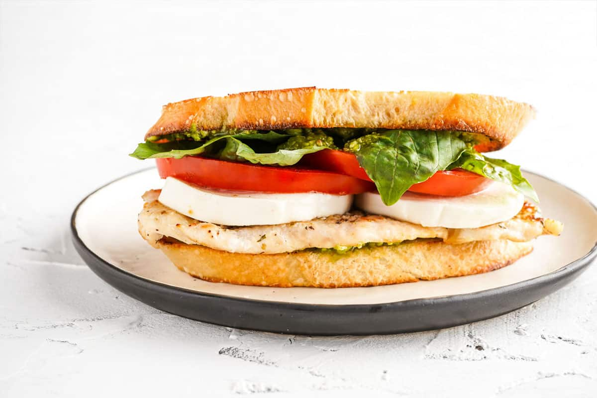 side view of sandwich with chicken breast mozzarella tomato and basil