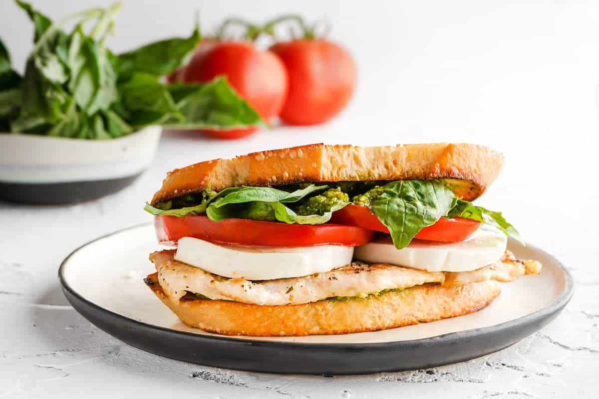 side view of chicken caprese sandwich with tomato and basil in the background