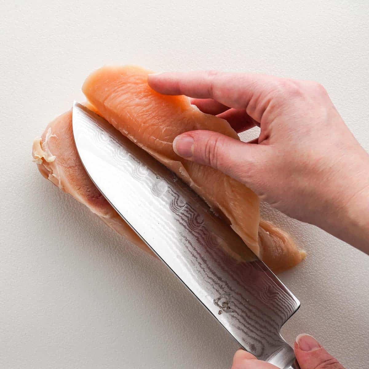 Hand pulling slice of chicken breast back as knife cuts through it