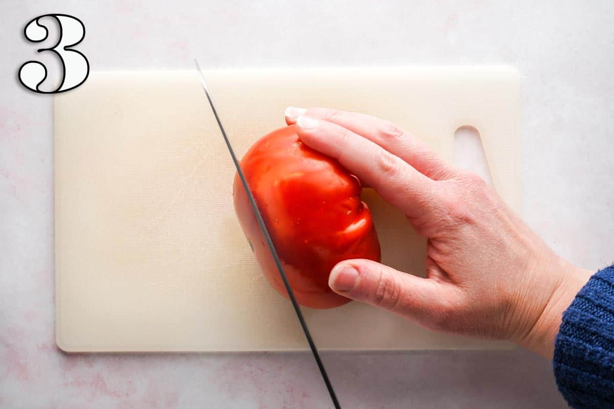 knife cutting a slice off a tomato being held on a cutting board