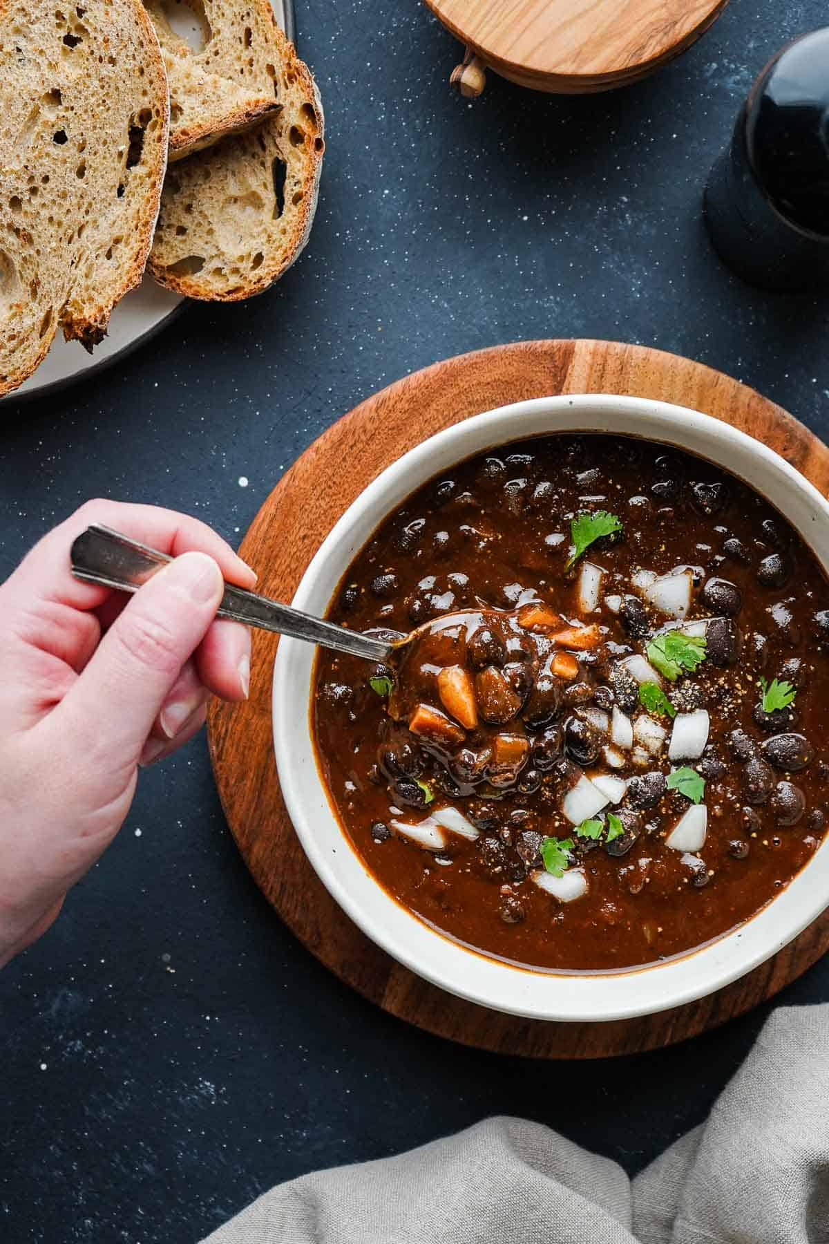 black bean soup in a bowl with a hand dipping a spoon inside with bread on the side