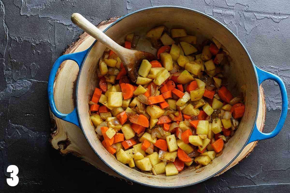 chopped apples carrots and onions in blue pot with wooden spoon