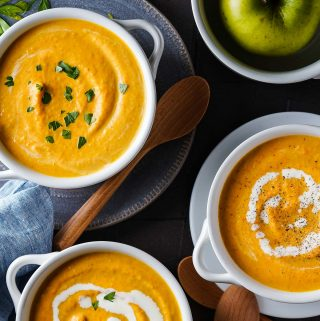 Carrot Pumpkin Apple Soup in 3 bowls with wooden spoons