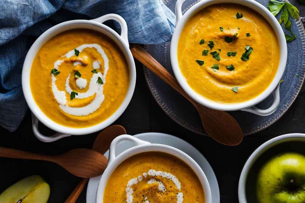Carrot Pumpkin Apple Soup in white bowls with wooden spoons on the side