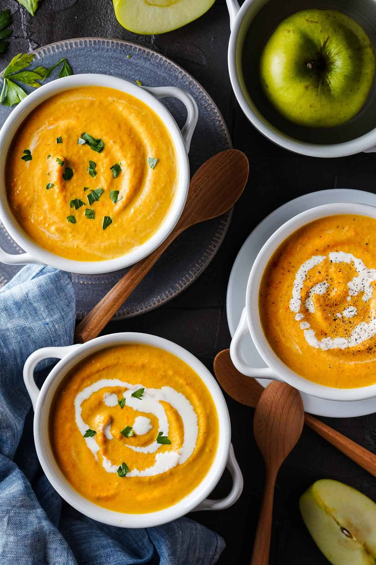 Carrot pumpkin apple soup in three bowls with wooden spoons