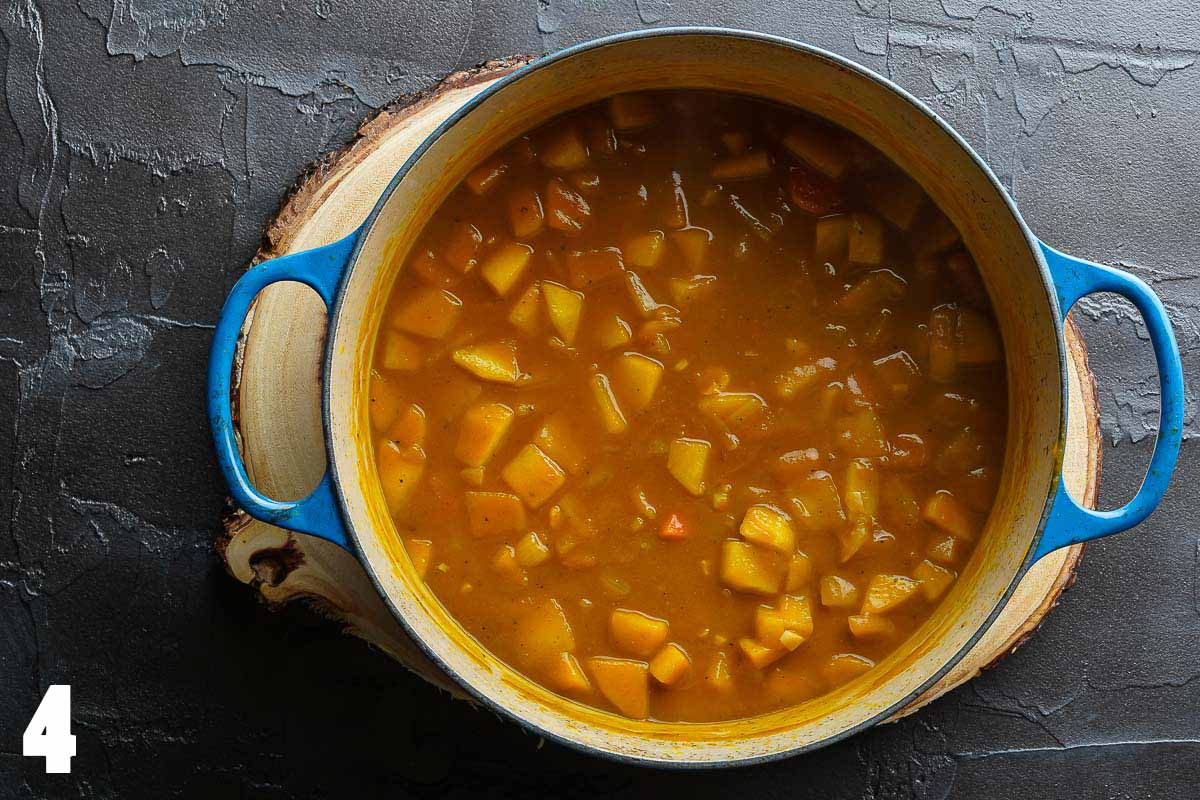 carrot pumpkin apple soup in blue pot prior to blending