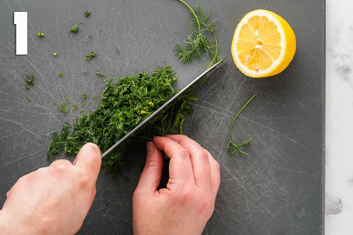fresh dill being finely chopped on grey cutting board