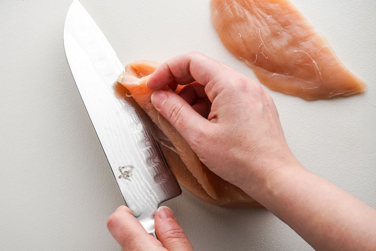 Knife cutting chicken breast into two pieces