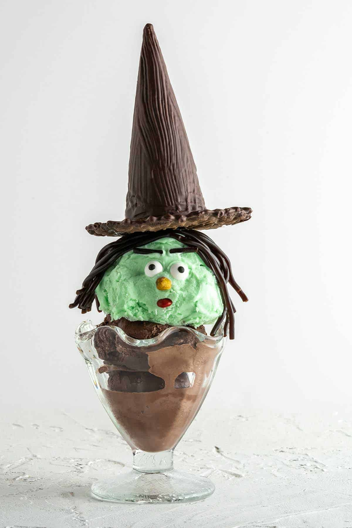 side view of witch Halloween sundae with white background