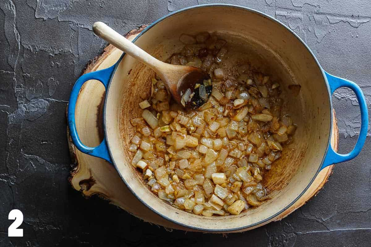 Onions garlic and spices browned in blue pot with wooden spoon