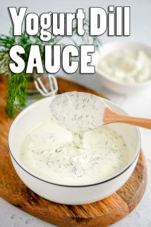 yogurt dill sauce in white bowl with wooden spoon and text overlay