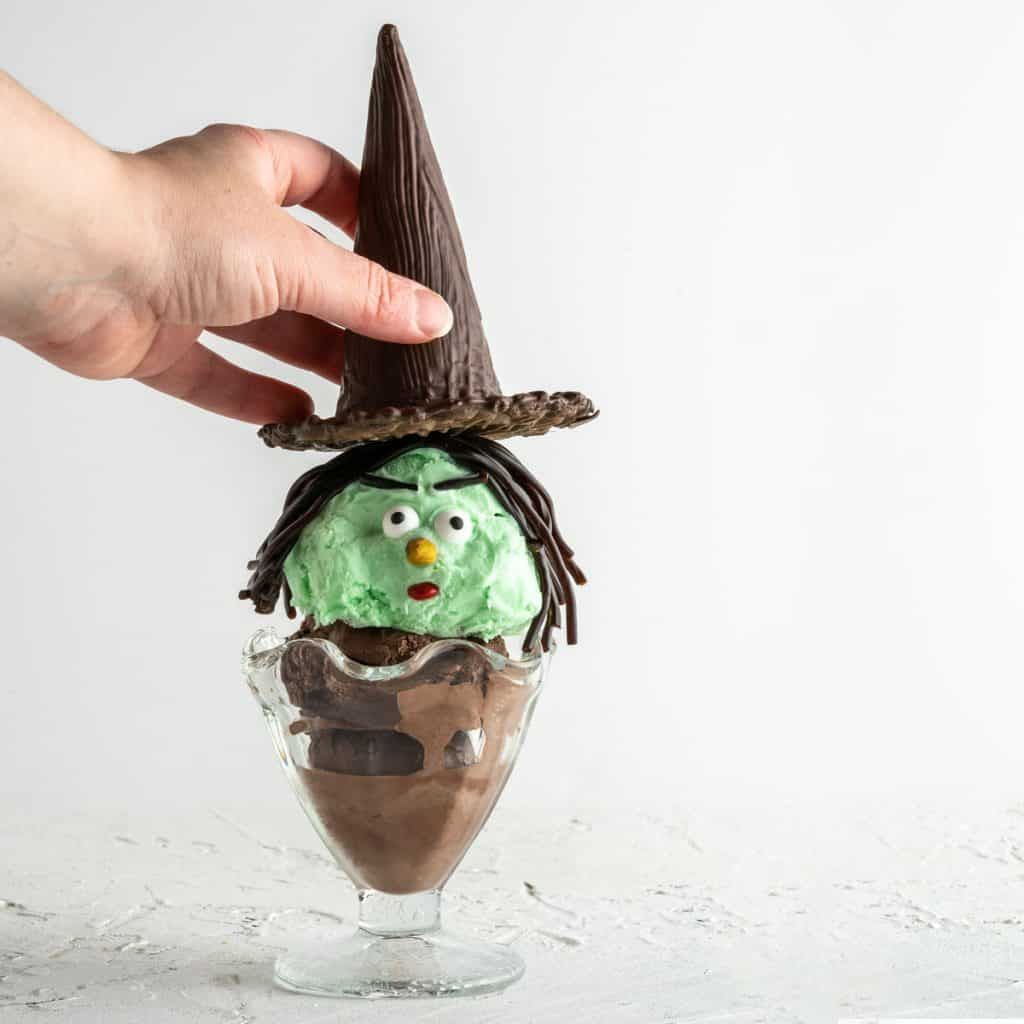 hand placing hat on top of Halloween witch ice cream sundae