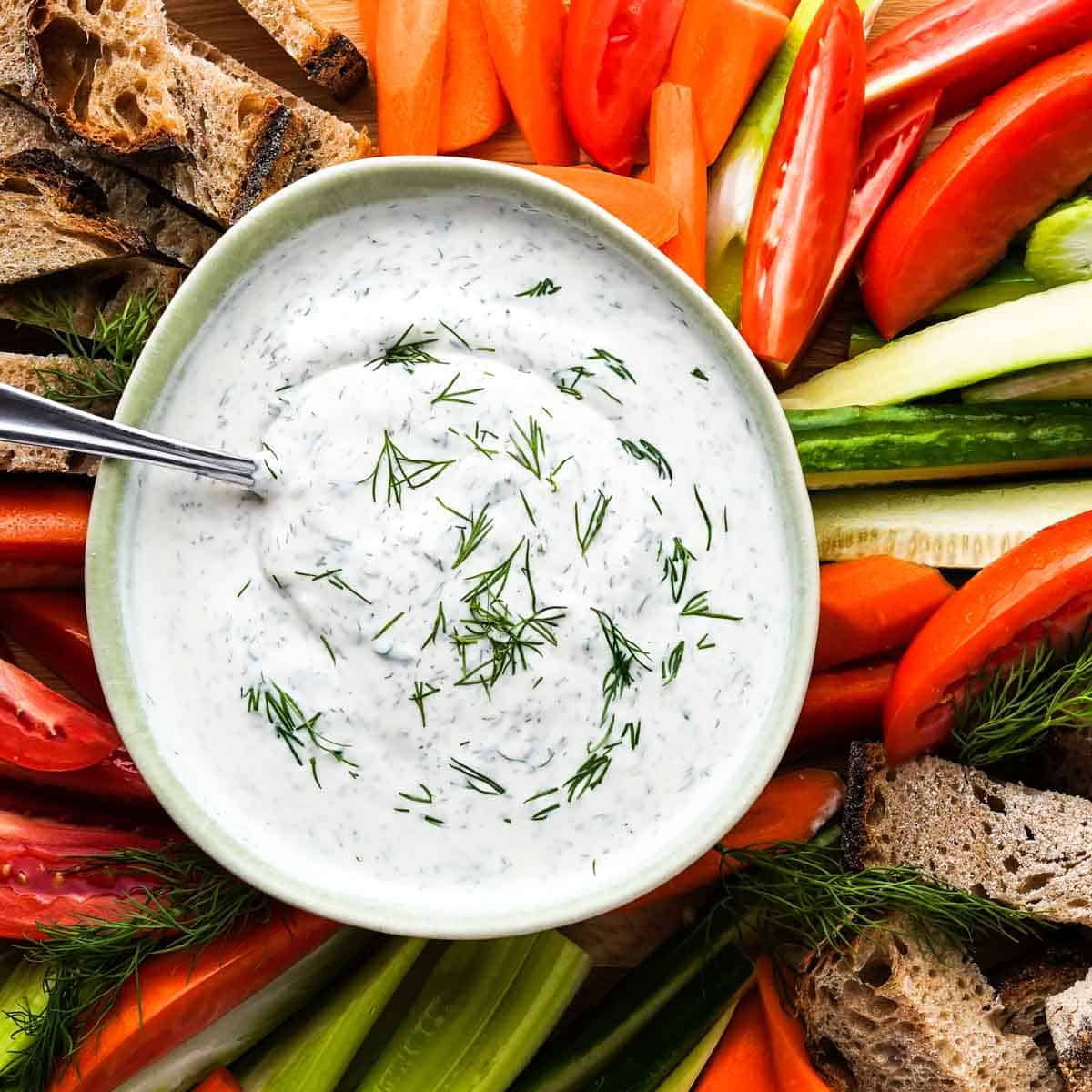 yogurt sauce in green bowl with veggies on the side