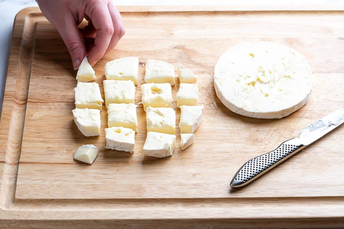 brie cut into small squares with hand holding a piece of brie